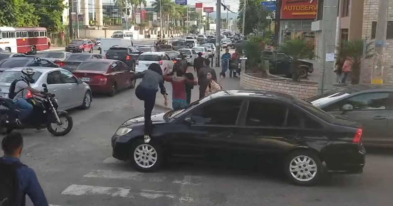 peatones pasan por encima de un coche en un paso de cebra