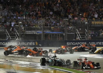 Ferrari's German driver Sebastian Vettel (front R) leads the pack as McLaren's Spanish driver Fernando Alonso (L) crashes during the Formula One Singapore Grand Prix in Singapore on September 17, 2017.  / AFP PHOTO / MOHD RASFAN