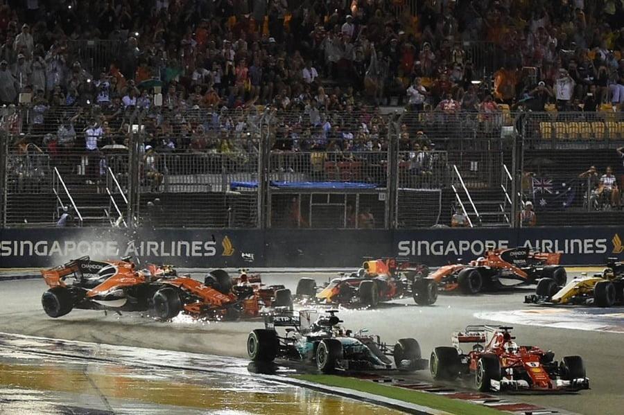 Ferrari's German driver Sebastian Vettel (front R) leads the pack as McLaren's Spanish driver Fernando Alonso (L) crashes during the Formula One Singapore Grand Prix in Singapore on September 17, 2017.  / AFP PHOTO / MOHD RASFAN